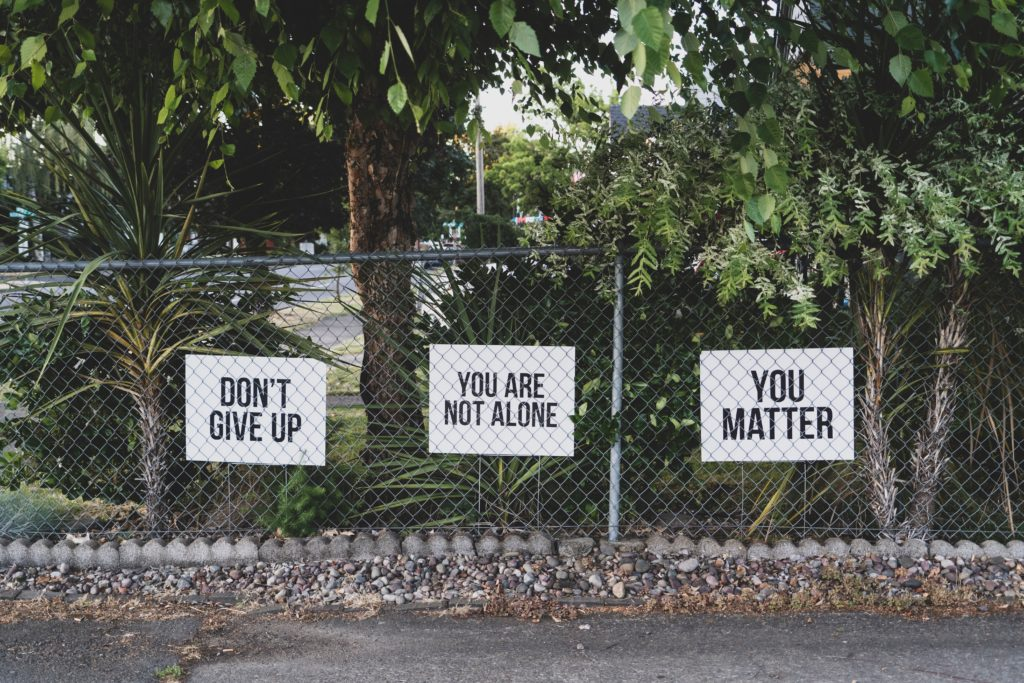 Three signs on metal fence that read Don't Give Up, Your Are Not Alone, and You Matter.