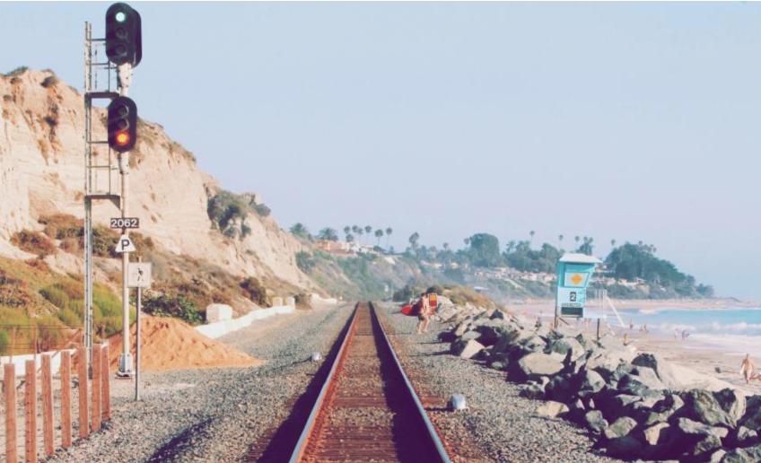 a green railroad signal over a red signal near a beach